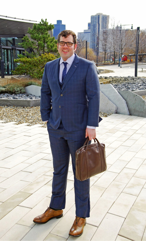 Suit, shirt, tie c/o Indochino; shoes by Allen Edmonds; bag by Jack Spade; glasses by Ralph Lauren Polo